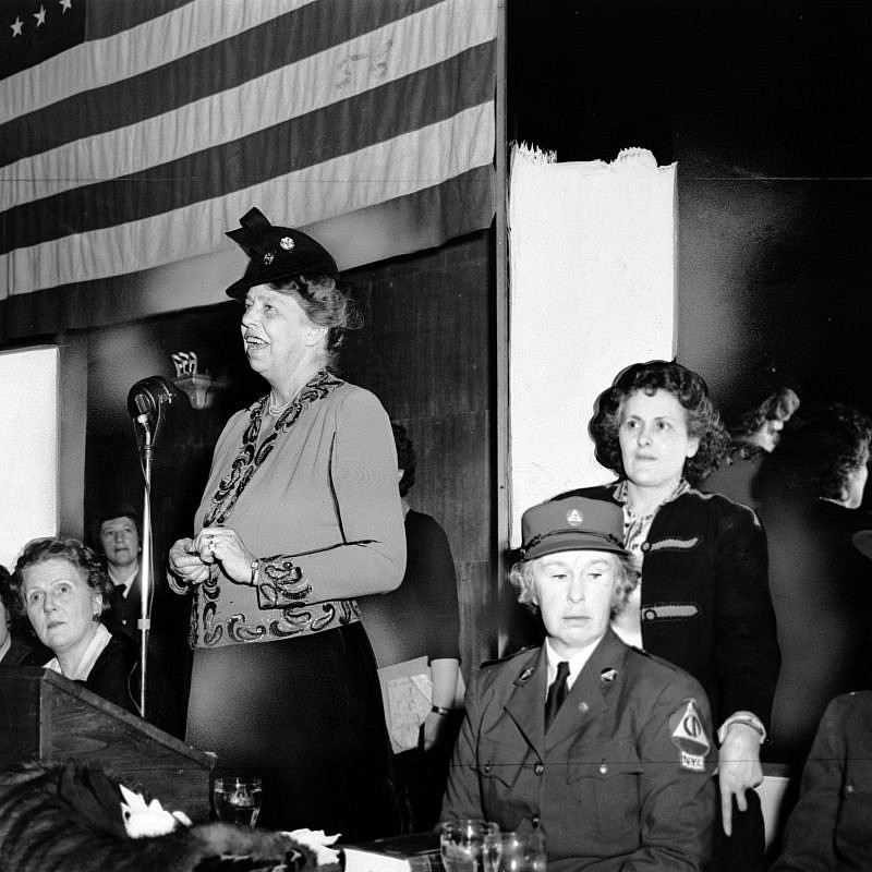 Eleanor Roosevelt speaks to a war-time audience, while Rose Pesotta and others listen. Credit: Flickr.