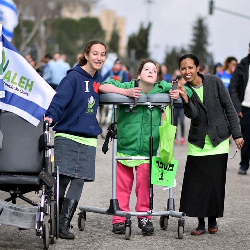 Volunteers and their young charge at a march for ALEH, Israel's network of care for children with severe complex disabilities. Credit: Courtesy.
