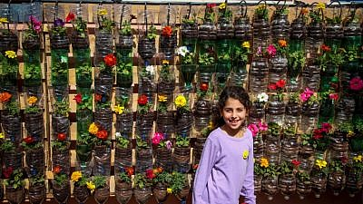 A girl stands by a wall full of flowers in plastic bottles at Amichai School in Kibbutz Yavne on March 24, 2017. Photo by Gershon Elinson/Flash90.
