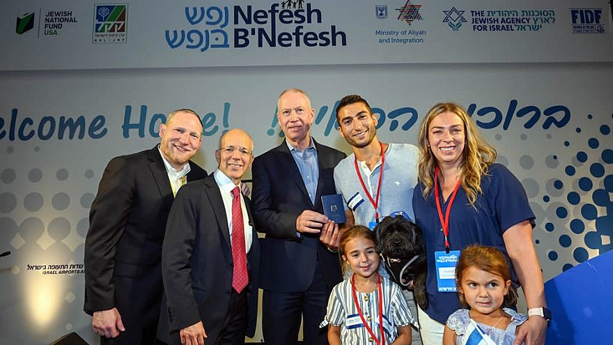 Evan Gershater, the 60,000th immigrant to Israel brought by Nefesh B'Nefesh, is given an Israeli identity card by Minister of Aliyah and Integration Maj. Gen. (ret.) Yoav Galant, and Nefesh B'Nefesh co-founders Rabbi Yehoshua Fass and Tony Gelbart. Photo by Shahar Azran.