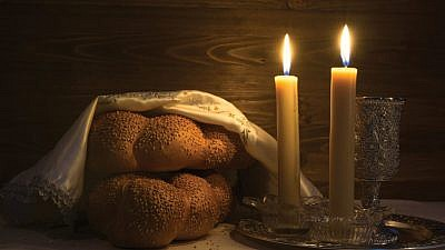 Challah and candles lit prior to the start of Shabbat.