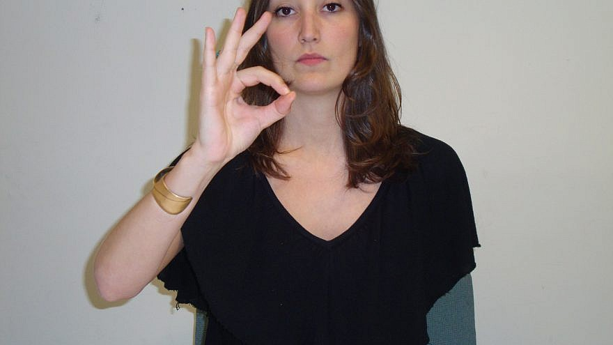 A woman giving the OK hand gesture. Credit: Wikimedia Commons.