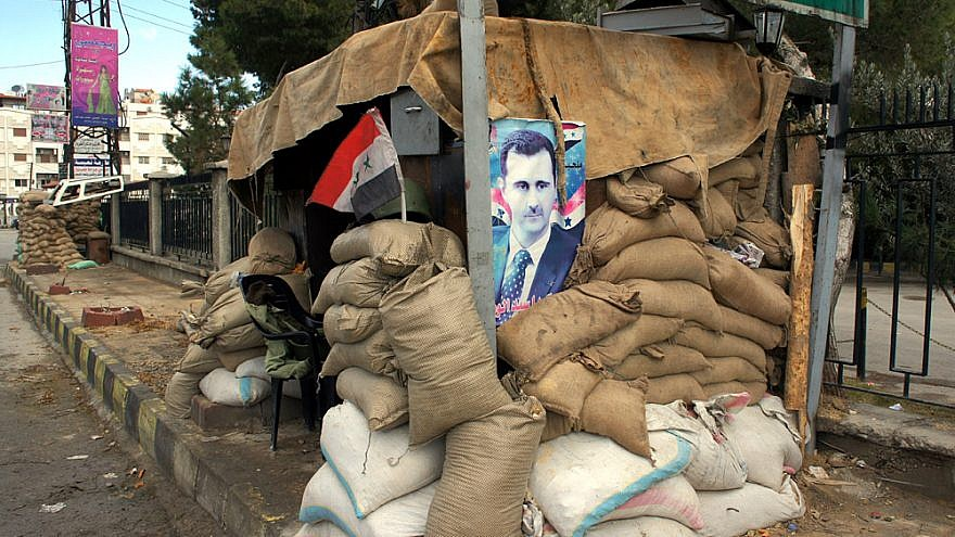 A poster of Syrian President Bashar Assad attached to a checkpoint on the outskirts of Damascus, Jan. 14, 2012.  Credit: Elizabeth Arrott via Wikimedia Commons.