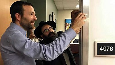 "California State Sen. Ben Allen, author of the state's landmark ""Mezuzah Bill,"" and Rabbi Mendy Cohen of Chabad of Sacramento, Calif., affix a ""mezuzah"" on Allen's office door after passage of the legislation. Credit: Legislative Jewish Caucus via Chabad.org/News."