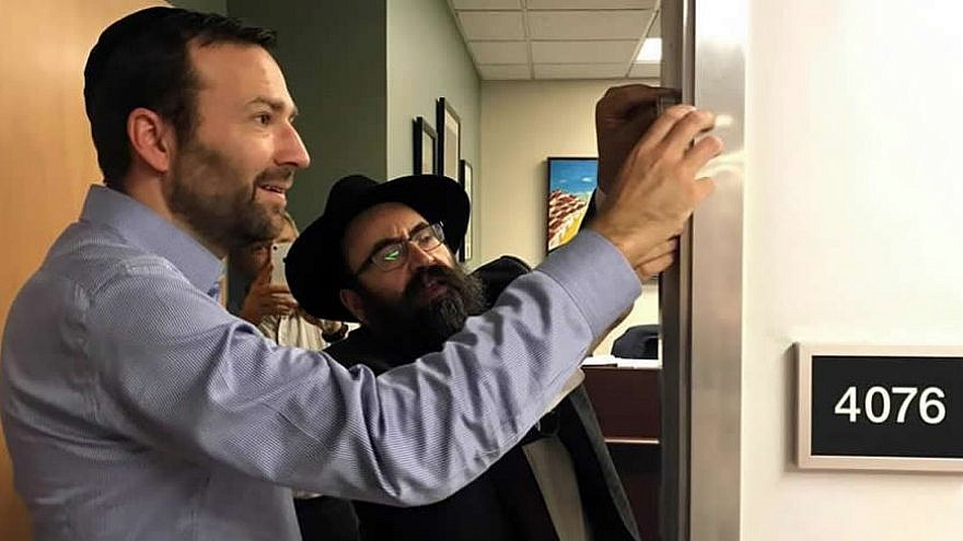 "California State Sen. Ben Allen, author of the state's landmark ""Mezuzah Bill,"" and Rabbi Mendy Cohen of Chabad of Sacramento, Calif., affix a ""mezuzah"" on Allen's office door after passage of the legislation. Credit: Legislative Jewish Caucus via Chabad.org/News."