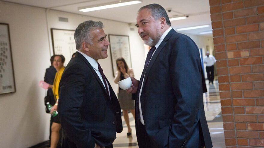 Yisrael Beiteinu leader Avigdor Lieberman (right) speaks with Yesh Atid Party leader Yair Lapid in the corridors of the Knesset on Nov. 16, 2015. Photo by Miriam Alsterl/Flash90.