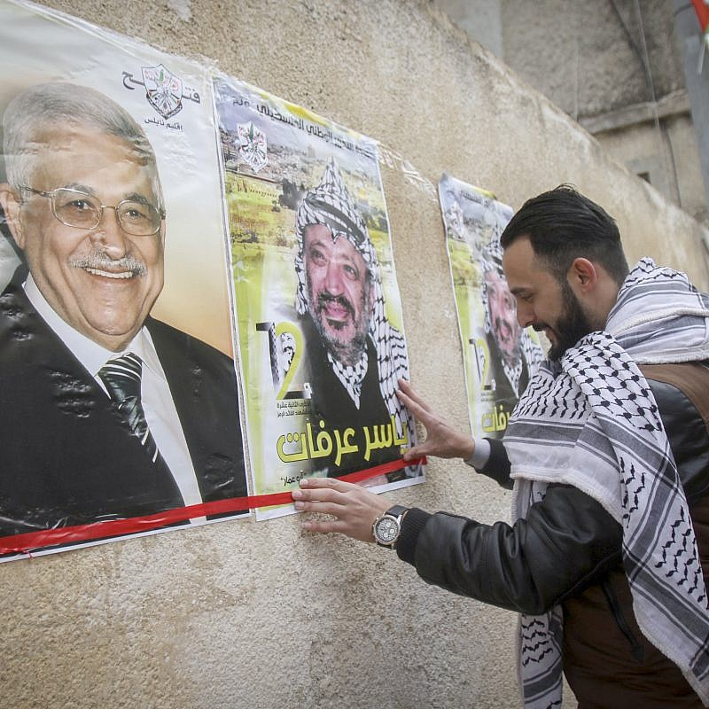 Palestinians hang posters depicting late Palestinian leader Yasser Arafat and Palestinian President Mahmoud Abbas, in the West Bank city of Nablus. March 14, 2017. Photo by Nasser Ishtayeh/Flash90