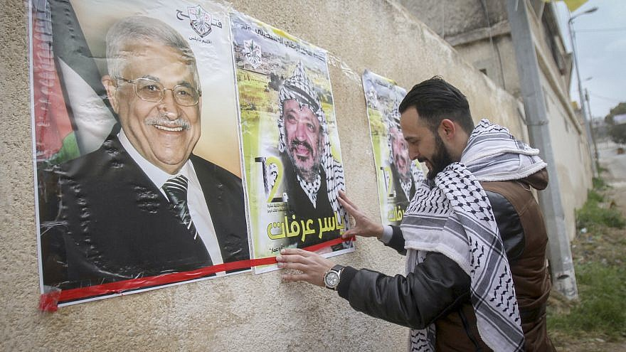 Palestinians hang posters depicting the late Palestinian chief Yasser Arafat and the current Palestinian leader Mahmoud Abbas in the West Bank city of Nablus, March 14, 2017. Photo by Nasser Ishtayeh/Flash90.