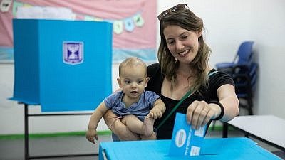 A woman holds her baby as she casts her ballot at a voting station in Jerusalem during the second round of Israeli elections on Sept. 17, 2019. Photo by Yonatan Sindel/Flash90.
