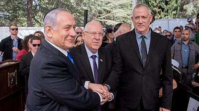 Israeli President Reuven Rivlin (center), Israeli Prime Minister Benjamin Netanyahu (left), and Blue and White leader Benny Gantz shake hands at a memorial ceremony for the late President Shimon Peres at the Mount Herzl cemetery in Jerusalem, Sept. 19, 2019. Photo by Yonatan Sindel/Flash90.