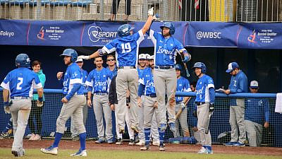 Danny Valencia, No. 19 (left, in the air) and Nick Rickles after Team Israel's win in Game 5 against South Africa. Photo by Margo Sugarman.