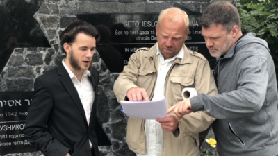 From left: Host Levs Perlovs, writer Andrejs Hramcovs and producer Eugene Levin filming at the Daugavpills Ghetto Memorial in Latvia. Photo by Jeff Hoffman.