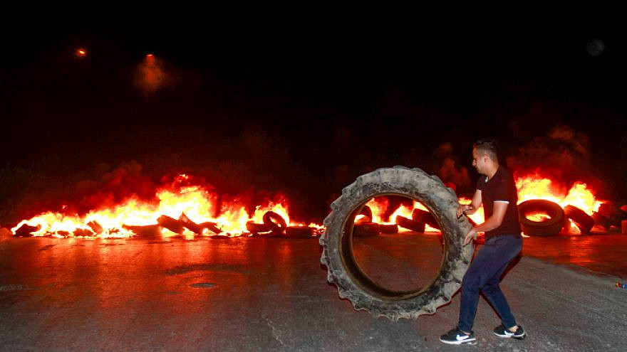 A Palestinian demonstrator burns tires near Joseph's Tomb in the West Bank city of Nablus on July 2, 2019, as thousands of Jews make their way to visit the grave. Photo by Nasser Ishtayeh/Flash90.