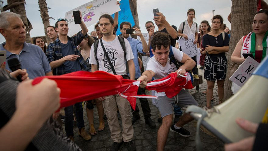 Israeli demonstrators tear a Turkish flag during protest march from the Turkish Embassy to the U.S. Embassy branch in Tel Aviv in support of the Syrian Kurds and against Turkey's incursion into Syria, Oct. 15, 2019. Photo by Miriam Alster/Flash90.