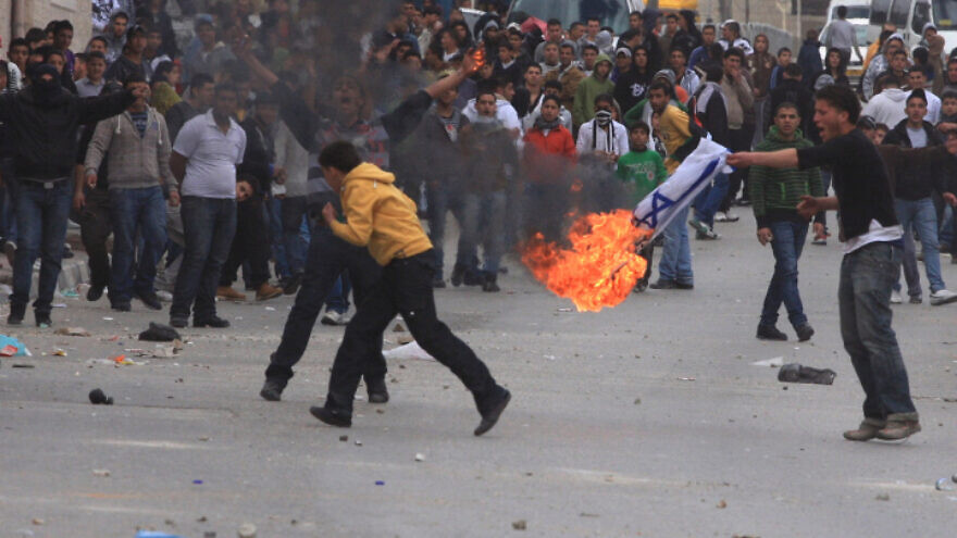 "Palestinians burn an Israeli flag during a ""day of rage"" riot at Qalandiya checkpoint near Ramallah in the West Bank, March 16, 2010. Photo by Issam Rimawi/Flash90."