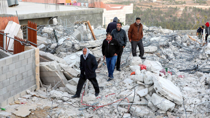Palestinians inspect the damage following the demolition by Israel of the family home of a suspect in the murder of Dvir Sorek, in the village of Beit Kahel near Hebron, Nov. 28, 2019. Photo by Wisam Hashlamoun/Flash90.