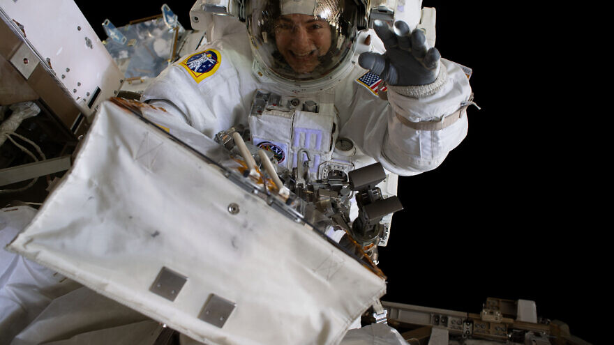 NASA astronaut Jessica Meir waves at the camera during a spacewalk with fellow NASA astronaut Christina Koch (out of frame). They ventured into the vacuum of space for seven hours and 17 minutes to swap a failed battery charge-discharge unit (BCDU) with a spare during the first all-woman spacewalk, Oct. 18, 2019. Credit: NASA via Wikimedia Commons.