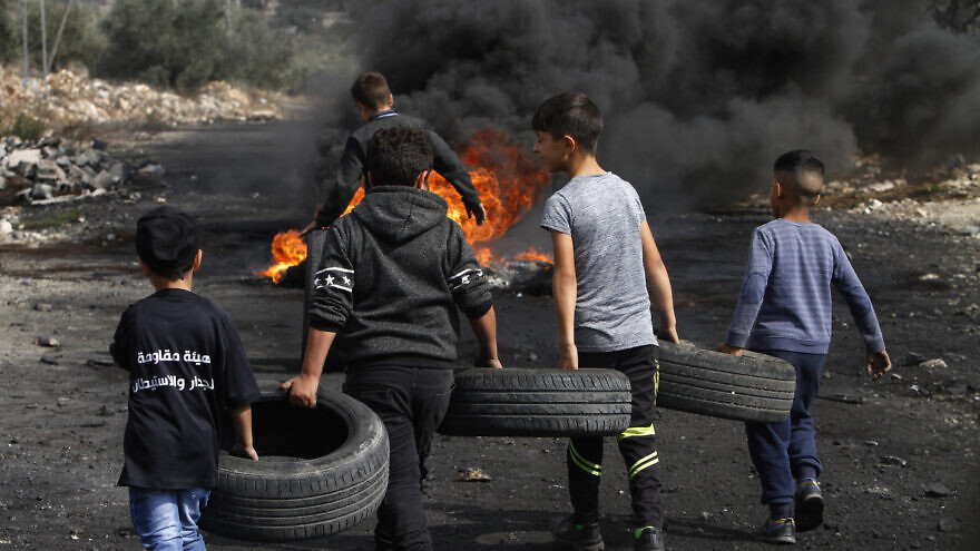 Palestinian boys carry tires to burn as part of clashes with Israeli forces during a protest in the village of Kfar Qaddum, near the West Bank city of Nablus, on Nov. 1, 2019. Both the Palestinian Authority and Hamas are roundly criticized for using children in violent protests. Photo by Nasser Ishtayeh/Flash90.
