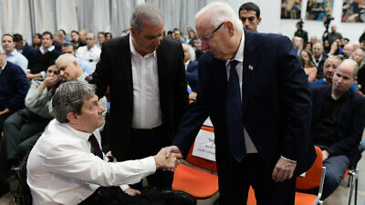 Israeli President Reuven Rivlin shakes hands with Idan Clayman, head of the IDF Organization for the Disabled, at an event in honor of Israeli soldiers disabled in the line of duty, at Beit Halochem in Tel Aviv on Dec. 15, 2019. Photo by Tomer Neuberg/Flash90.