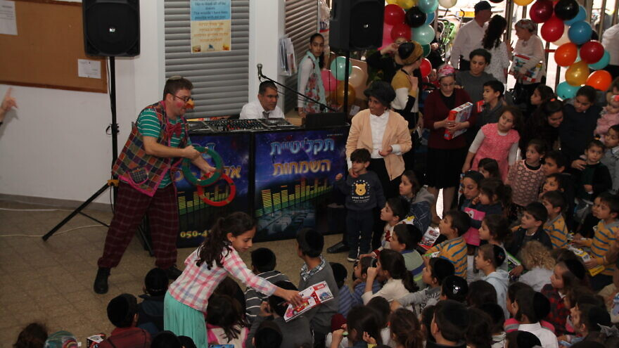 Ohr Meir & Bracha: The Terror Victims Support Center hosts an annual Hanukkah party for hundreds, complete with a clown and toy giveaways, December 2019. Credit: Courtesy.