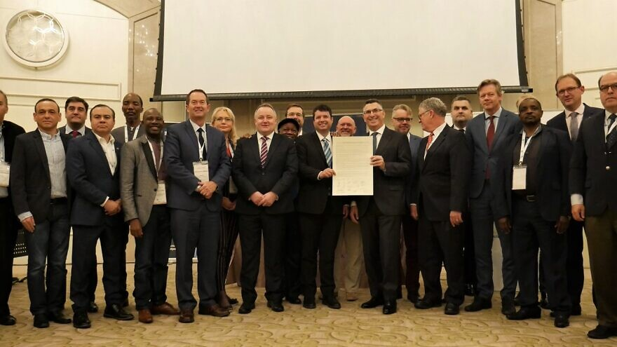 Faith-based pro-Israel parliamentarians in Jerusalem for the Israel Allies Foundation's (IAF) annual Chairman's Conference hand a resolution calling for elected officials worldwide to oppose the BDS movement to Likud Party Knesset member Gideon Sa'ar, December 2019. Credit: Jerusalem East Gate Foundation.