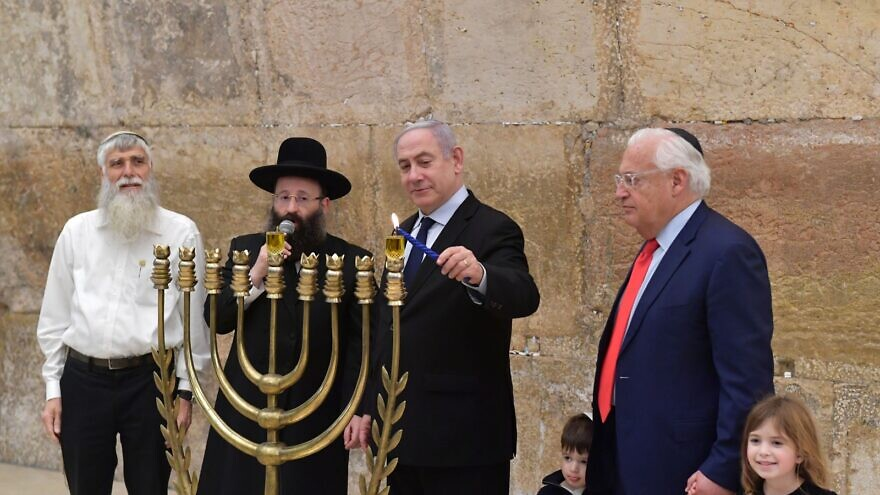 """Israeli Prime Minister Benjamin Netanyahu and U.S. Ambassador to Israel David Friedman (right) light the first Hanukkah candle at the Western Wall in Jerusalem. To Netanyahu's left is Rabbi Shmuel Rabinovitch, rabbi of the Western Wall, and next to him is Mordechai """"Suli"""" Elias, director of the Western Wall Heritage Foundation, Dec. 22, 2019. Photo by Koby Gideon/GPO."""