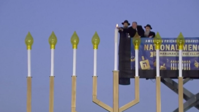 """U.S. Interior Secretary David Bernhardt (center) helps light the shamash (""""helper candle"""") of the National Menorah on the Ellipse near the White House in Washington, D.C., on Dec. 22, 2019, assisted by Rabbi Levi Shemtov (left), executive vice president of American Friends of Lubavitch (Chabad), and his father, Abraham Shemtov. Source: Screenshot."""