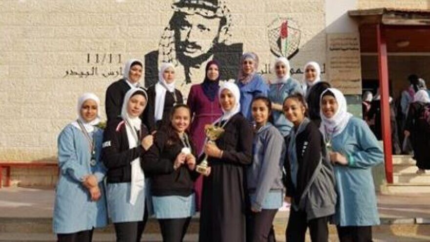 Palestinian girls pose in front of their school in Bethlehem on Nov. 19, 2019. Visible on the wall by the school entrance is a plaque honoring Ayat al-Akhras, an 17-year-old suicide bomber that killed two Israelis in 2002. Credit: Palestinian Media Watch.