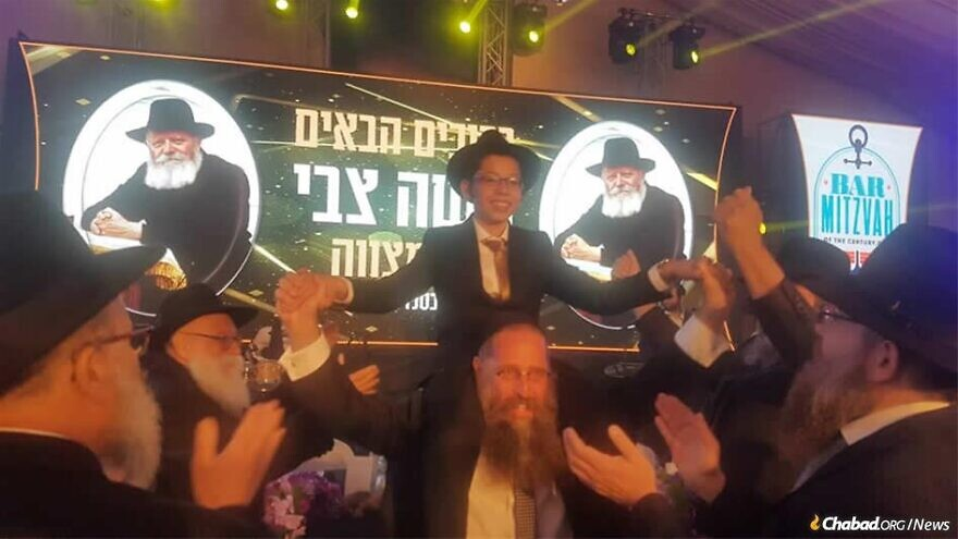 A celebratory bar mitzvah crowd dances with Moshe Holtzberg, orphaned in the Mumbai Chabad center massacre that took the lives of his parents 11 years ago this week. Credit: Chabad.org/News.