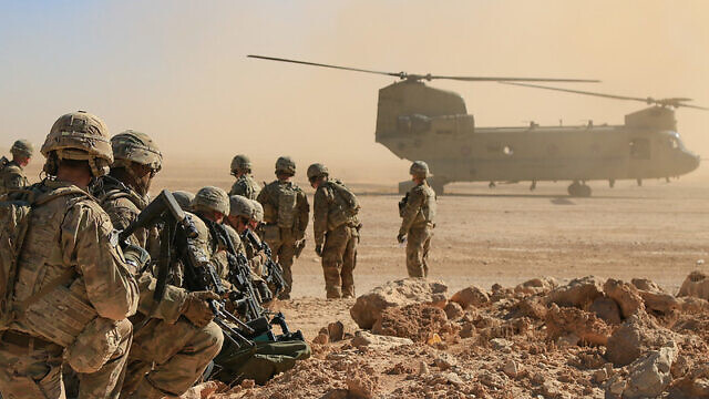 """U.S. soldiers assigned to Bandit Troop, 1st Squadron, 3rd Cavalry Regiment and deployed in support of Combined Joint Task Force """"Operation Inherent Resolve"""" await aerial extraction via CH-47 Chinook during an aerial response force live-fire training exercise in Iraq, Oct. 31, 2018. Credit: 1st Lt. Leland White/U.S. Army National Guard."""