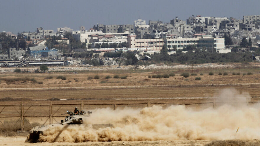 An Israeli Merkava tank moves along the border with Gaza (background), as Israeli forces prepare to clear the area, on Aug. 06, 2014. Photo by Miriam Alster/Flash90.