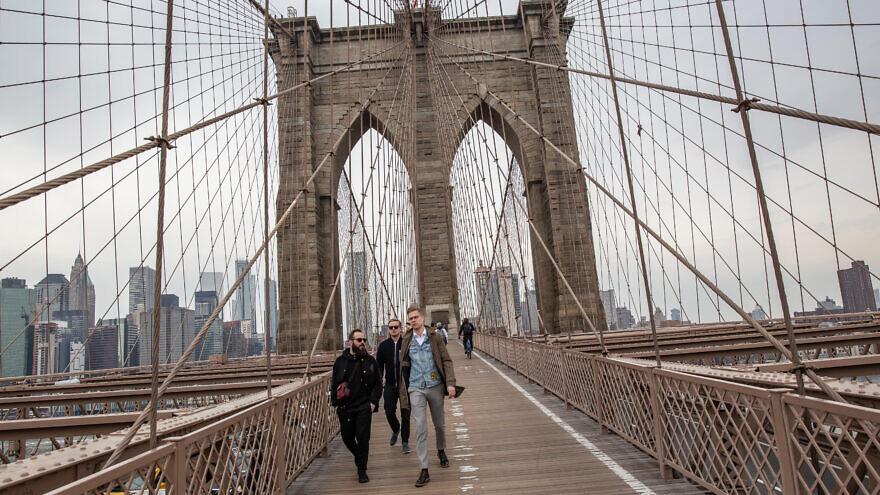 People walk across the Brooklyn bridge in New York City. April 12, 2018. Photo by Aharon Krohn/Flash90.