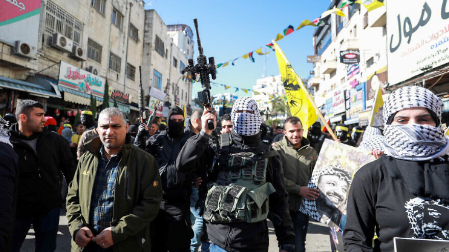 Palestinian Fatah members hold up their weapons during a rally marking the 55th anniversary of the founding of the Fatah movement, in the West Bank city of Ramallah, Dec. 31, 2019. Photo by Flash90.