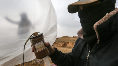 Palestinians prepare a flammable object to be flown towards Israel, near the border with the Gaza Strip, on Jan. 18, 2020. Photo by Abed Rahim Khatib/Flash90.