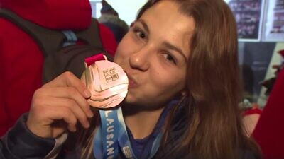Israeli alpine skier Noa Szollos kissing her gold medal. Source: Screenshot.