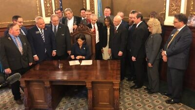 South Dakota Gov. Kristi Noem signs an executive order prohibiting state offices from doing business with companies that boycott Israel, Jan. 14, 2020. Credit: American Jewish Committee.