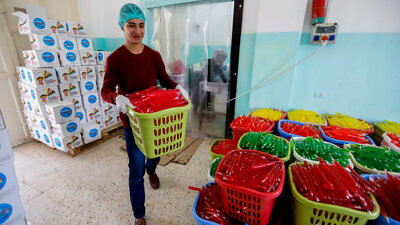Palestinian workers sort ice pops at a factory in the West Bank village of Tafouh, near Hebron, on April 16, 2019. Photo by Wisam Hashlamoun/Flash90.