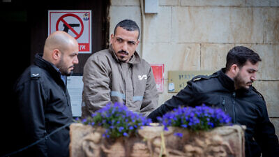 Sanad al-Turman, the suspect in the car-ramming attack in Jerusalem on Feb. 6, 2020, is escorted by prison guards outside the Jerusalem Magistrate's Court on Feb. 7, 2020. Photo by Yonatan Sindel/Flash90.