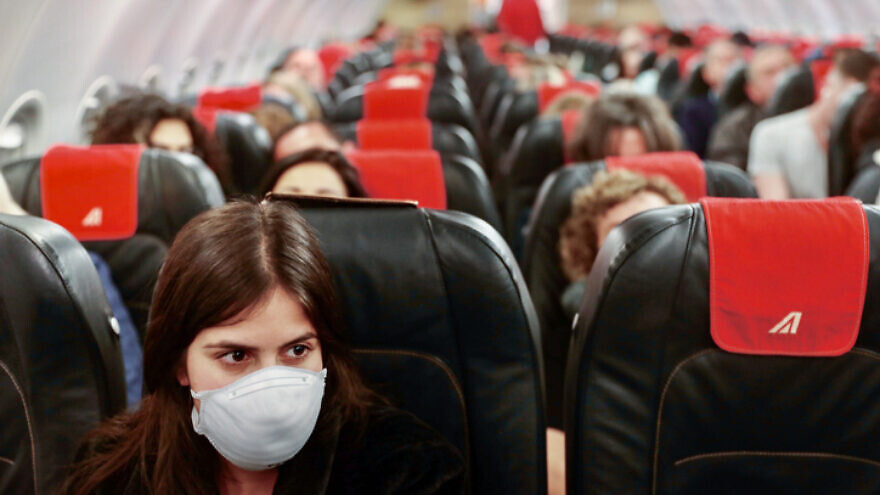 A woman wears a face mask for fear of the SARS-Cov-2 virus on a flight from Tel Aviv to Rome on Feb. 21, 2020. Photo by Nati Shohat/Flash90.