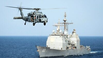 An HH-60H Sea Hawk helicopter passes the guided-missile cruiser USS Normandy in the Arabian Gulf in September 2015. Credit: Anna Van Nuys/U.S. Navy.