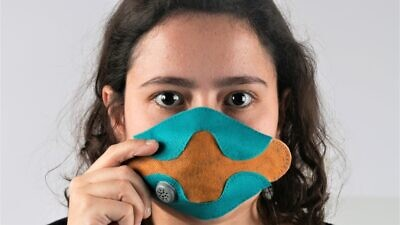 Yael Mordechay, a student in the industrial design department of the Bezalel Academy of Art and Design in Jerusalem, displays the protection mask against bacteria and viruses that she designed. Credit: Courtesy.