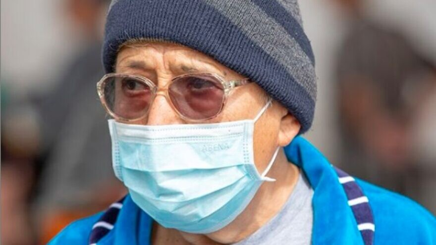 An older man in Israel wears a face mask to protect himself from the coronavirus, March 2020. Credit: Photo by Jordan Hay/IFCJ.