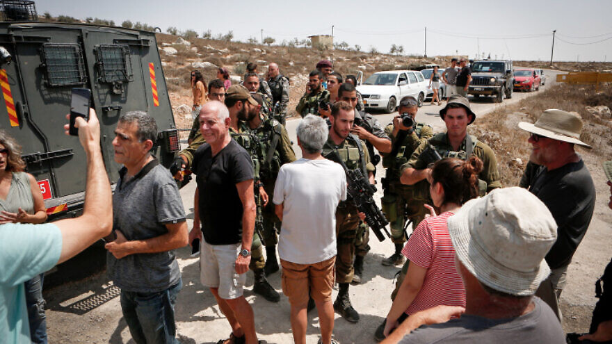 Israeli soldiers detain Israeli left-wing activists during a tour conducted by NGO Breaking the Silence in Mitzpe Yair, near Hebron in Judea and Samaria, on Aug. 31, 2018. Photo by Wisam Hashlamoun/Flash90.