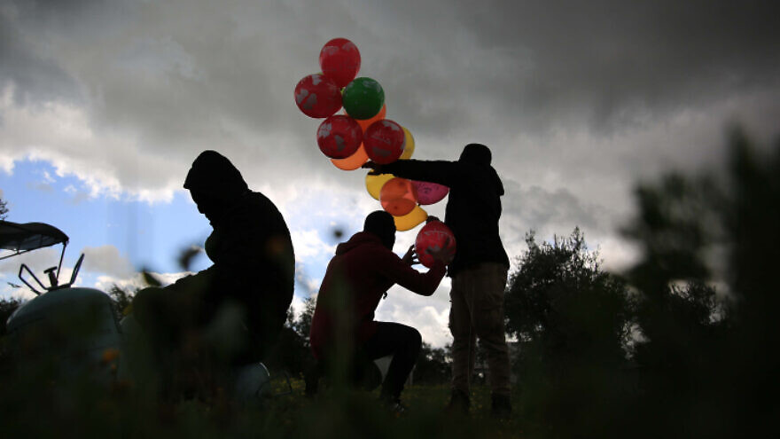 Palestinians prepare an incendiary device to be flown towards Israel, near the Israel-Gaza border in the central Gaza Strip, Feb. 10, 2020. Photo by Ali Ahmed/Flash90.