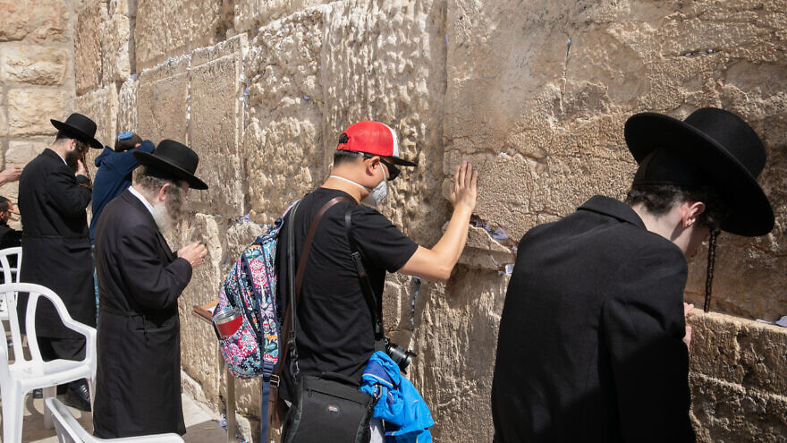 An American tourist wearing a face mask for fear of the coronavirus prays at the Western Wall in the Old City of Jerusalem on Feb. 27, 2020. Photo by Olivier Fitoussi/Flash90.