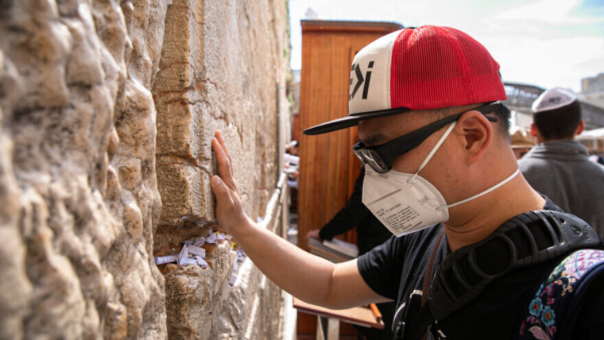 An American tourist wears a face mask to protect against germs while prayering at the Western Wall in the Old City of Jerusalem on Feb. 27, 2020. Photo by Olivier Fitoussi/Flash90.