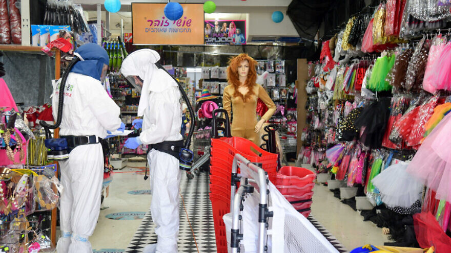 Workers disinfect a shop in Or Yehuda, Israel, after a shop worker who recently returned from a visit to Italy tested positive for coronavirus, Feb. 28, 2020. Photo by Flash90.