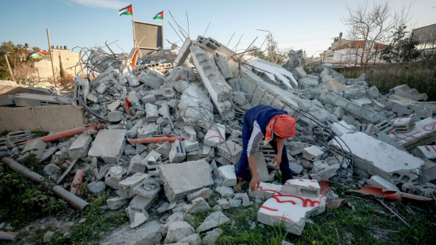 A Palestinian man walks on the rubble of the family house of suspected Palestinian terrorist Yazan Mughamis after it was demolished by Israeli forces in the West Bank town of Birzeit on March 5, 2020. Photo by Flash90.