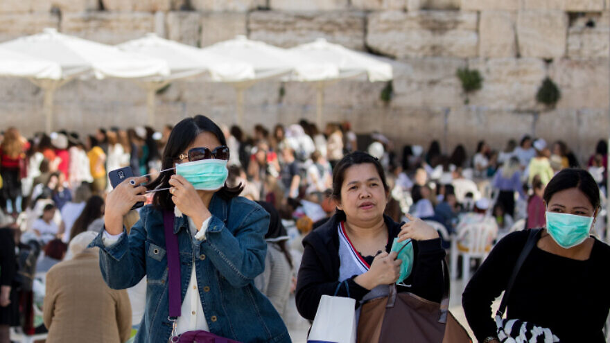 Tourists wear face masks for fear of the coronavirus while touring the Western Wall in the Old City of Jerusalem on March 5, 2020. Photo by Olivier Fitoussi/Flash90.