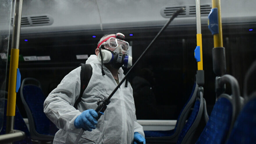 Workers wearing protective suits disinfect a bus in Tel Aviv as a preventive measure amid fears over the spread of coronavirus, March 9, 2020. Photo by Tomer Neuberg/Flash90.